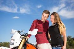 Junge Paare, die neben einem Motorrad stehen Stockfoto