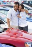 Junge Paare, die neue Autos betrachten Lizenzfreie Stockfotos