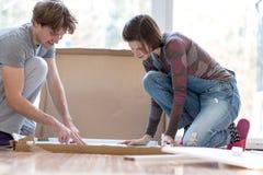 Junge Paare, die neues furinture zusammenfügen Stockbilder