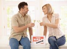 Junge Paare, die neues Haus feiern Stockbild