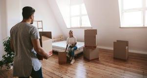 Junge Paare, die in neues Haus sich bewegen Stockbilder