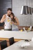 Junge Paare, die Orangensaft morgens essen Lizenzfreie Stockfotografie