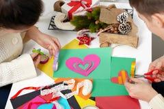 Junge Paare, die Origamidekorationen für Valentinstag, die Draufsicht - romantisch und Liebeskonzept machen Stockfotos