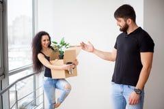 Junge Paare, die Pappschachteln am neuen Haus auspacken Bewegliches Haus stockfoto