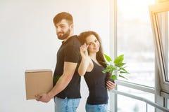Junge Paare, die Pappschachteln am neuen Haus auspacken Bewegliches Haus stockfotos