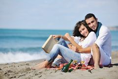 Junge Paare, die Picknick auf dem Strand genießen Lizenzfreie Stockbilder