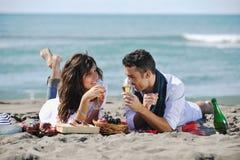 Junge Paare, die Picknick auf dem Strand genießen Lizenzfreie Stockfotos