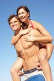 Junge Paare, die Piggyback am Strand-Feiertag genießen Stockfoto