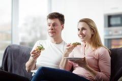 Junge Paare, die Pizza essen stockfotos