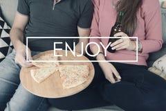 Junge Paare, die Pizza mit Zeichen essen Lizenzfreies Stockbild
