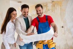 Junge Paare, die Pläne ihres Hauses mit Arbeitskraft schauen Stockbilder
