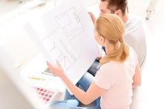 Junge Paare, die Plan seines Hauses schauen Lizenzfreie Stockbilder