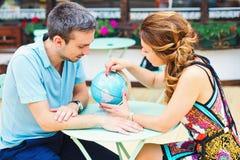 Junge Paare, die Pläne für ihr folgendes Reiseziel machen Stockbild