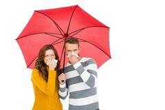 Junge Paare, die Regenschirm halten und Nase abwischen Stockbild