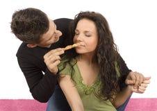 Junge Paare, die Rollenkuchen sich speisen stockbilder