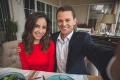 Junge Paare, die romantisches im Restaurant umarmt zu Abend essen, Fotonahaufnahme nehmend Stockbilder