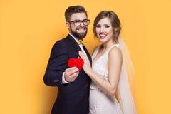 Junge Paare, die rotes Inneres anhalten lizenzfreies stockbild