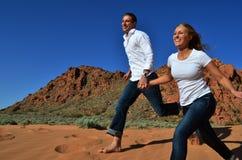 Junge Paare, die in Sand und Händchenhalten laufen lizenzfreie stockfotografie