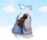 Junge Paare, die an sein kommendes Baby im Schwangerschaftskonzept zusammen denken sitzen Stockbild