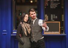 Junge Paare, die selfie auf Smartphone auf der Stra?e nahe dem Caf? nehmen stockfotos