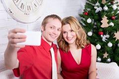 Junge Paare, die selfie Foto vor Weihnachtsbaum machen Lizenzfreie Stockbilder