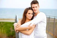 Junge Paare, die sich umfassen Stockbild