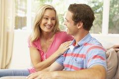 Junge Paare, die sich zu Hause auf Sofa entspannen Stockfoto