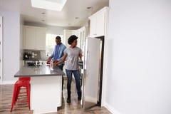 Junge Paare, die sich zusammen in der Wohnungs-Küche entspannen Stockfotos