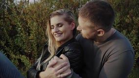 Junge Paare, die sitzend auf Rasen im Herbstpark sich amüsieren stock video
