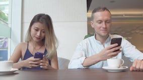 Junge Paare, die Smartphones betrachtend sich ignorieren stockfoto