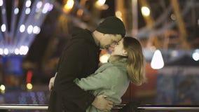 Junge Paare, die Spaß auf einem Vergnügungsparkdatum nachts haben