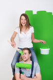 Junge Paare, die Spaß haben, wie sie ihr Haus malen Stockfotografie