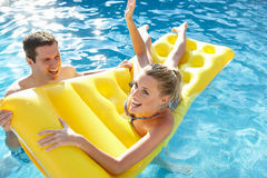Junge Paare, die Spaß im Pool haben Stockbild