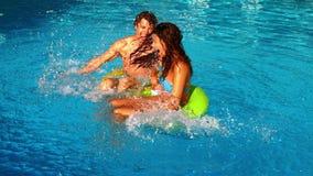 Junge Paare, die Spaß im Swimmingpool spritzen und haben stock video
