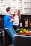 Junge Paare, die Spaß in der Küche haben Stockbilder