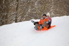 Junge Paare, die Spaß im Schnee haben Stockfotos