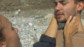 Junge Paare, die am Strand sitzen stock footage