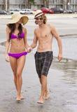 Junge Paare, die am Strand spielen Stockfotografie