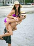 Junge Paare, die am Strand spielen Lizenzfreie Stockfotos