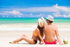Junge Paare, die am tropischen Strand mit frischen Kokosnusscocktails sich entspannen Lizenzfreie Stockbilder