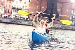 Junge Paare, die um die Stadt canoeing sind Lizenzfreie Stockfotografie