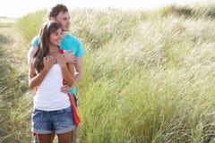 Junge Paare, die unter Dünen stehen Lizenzfreie Stockfotos