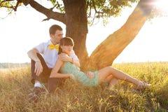 Junge Paare, die unter dem Baum liegen Lizenzfreies Stockfoto