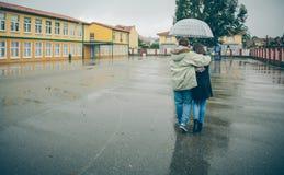 Junge Paare, die unter dem Regenschirm geht in a umfassen Stockbilder