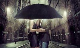 Junge Paare, die unter dem Regenschirm sich verstecken Lizenzfreie Stockfotos