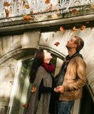Junge Paare, die unter Laubfall stehen Lizenzfreie Stockfotos
