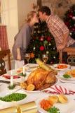 Junge Paare, die unter Mistel am Weihnachten küssen Stockfoto