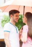 Junge Paare, die unter Regenschirm und dem Lächeln stehen Lizenzfreie Stockfotos