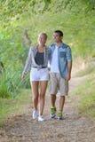 Junge Paare, die in Wald gehen stockfotos