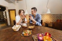 Junge Paare, die Wein am Restauranttisch essen Stockbild